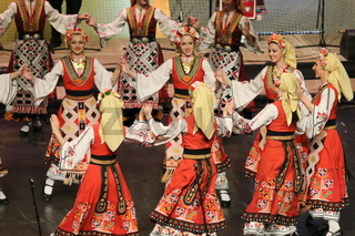 People in traditional folklore costumes perform folk dance Bulgarian horo