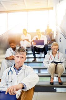 Gruppe Ärzte sitzt in Pause auf Treppe in Klinik