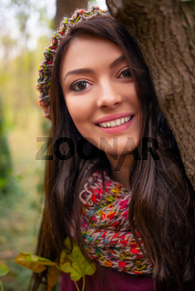 A gorgeous romantic young woman with beautiful long brown hair, in autumn park outdoors scenery, looking at the camera and smiling happy. Headshot portrait in natural light, retouched, vibrant colors