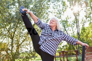 Vitale Senior Frau beim Dehnen auf einem Bein