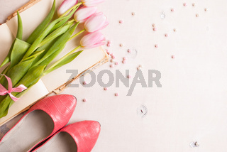 Pink tulips with women`s shoes over white wooden table. Spring chic background