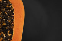 Half of ripe papaya with seed on a black plates and with a green plants on background. Slices of sweet papaya. Halved papayas. Healthy exotic fruits. Vegetarian food.