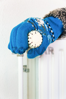 Hand wearing glove turns heating valve in winter