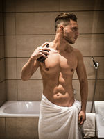 Young man in bathroom, spraying cologne or perfume