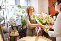 Florist verkauft einen bunten Blumenstrauß