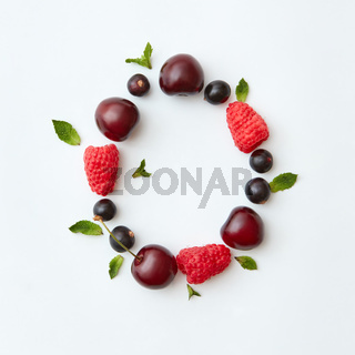 Natural berry pattern of letter O english alphabet from natural ripe berries - black currant, cherries, raspberry, mint leaf isolated on a white background.