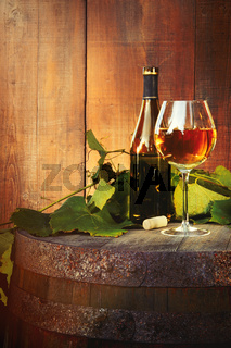 White wine bottle and glass on old barrel