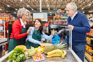 Verkäuferin hilft Azubi an der Supermarkt Kasse
