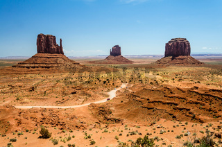 Dirt road with cars and mesa mountains in Monument Valley