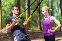 Young active people training with fitness straps outdoors.