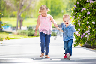 Young Sister and Brother Holding Hands And Walking At The Park