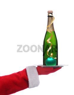 Santa Claus holding a serving tray with a Bottle of Champagne, gold ribbon and ornament over a white background.