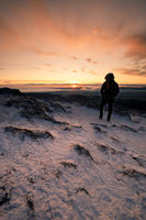 Hiker is standing on a Mountain Peak watching the Sunrise in Winter