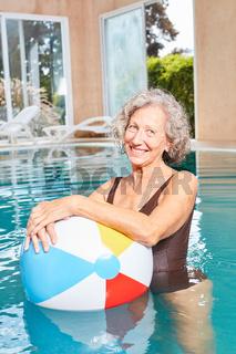 Senior Frau mit einem bunten Ball im Pool