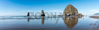 Tourists and locals enjoying the beach with Haystack Rock in the background at Cannon beach, Oregon, USA.