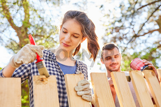 Grundieren und Lackieren von Holzzaun im Garten