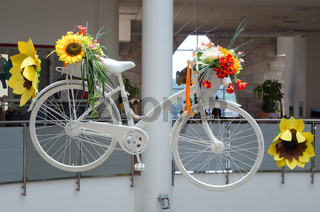 Idea for interior with white bicycle with flowers. An old bicycle painted in white with artificial