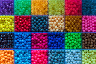 Many small beads are arranged in the box