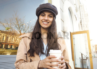 Pretty girl stand on the street with cup of coffee by the cafe wearing trench coat and cap