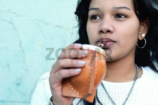 Young latin woman drinking traditional yerba mate tea.
