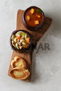 Crock bowls of fresh homemade Chicken Noodle and Tomato Soup on a cutting board with garlic toast