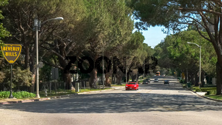 BEVERLY HILLS, CA, USA -AUGUST 25 2015: a luxury red sports car drives past the beverly hills sign in los angeles