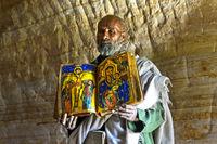 Priester der Felsenkirche Mikael Mellehayzengi zeigt das Buch Wunder der Maria, Äthiopien