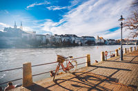 city bicycle with basket on the steering wheel of red color on the quay near the river Rhine in Switzerland against the backdrop of old city and authentic houses and cathedral on sunny day in winter