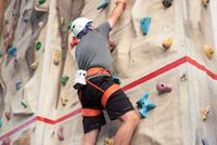 Sporty man practicing indoor rock climbing in climbing gym.