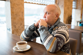 Pensive elderly man in modern cafe
