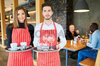 Mann und Frau als Service Kellner Team mit Tablett