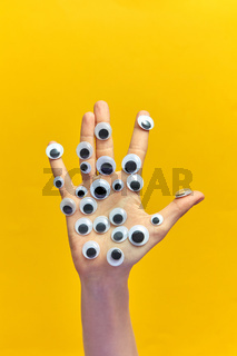 Woman's hand with plastic eyes on an yellow background.