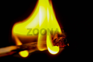 Match in flames burning down in front of black background