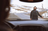 Traveller on the rural road trying to stop a car for assistance