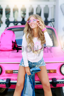Blonde Girl in summer near pink retro car