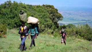 local porters carrying gear and equipment hike towards the summit of Mount Meru in Arusha National Park in Tanzania