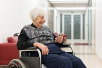 Lonley elderly 95 years old woman sitting at the wheelchair using modern mobile phone.