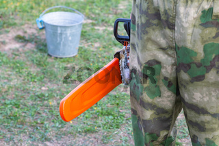worker in camouflage uniform stands with a chainsaw, the blade in an orange protective case against the background of the earth and an iron bucket