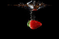 fresh healthy strawberry falling into water and injected and produced bubbles with black background
