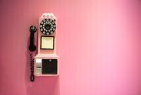 Old phone hanging on a pink wall