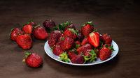 Fresh strawberries in ceramic bowl on dark wooden background. Selective focus. - Image