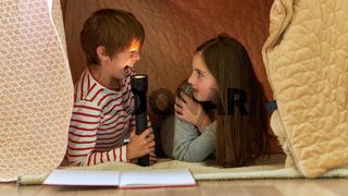 Kinder mit Taschenlampe spielen unter Decke