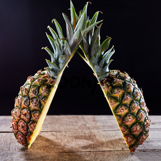 Tropical ripe fruit pineapple with green leaves presented on a wooden table around a dark background with copy space.