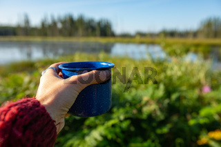 Person holding up a cup of coffee or tea