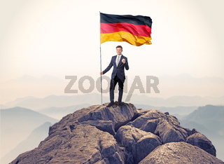 Businessman on the top of a rock holding flag