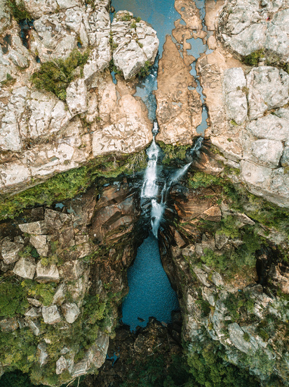 Overhead views waterfall flowing into rock pool at base of cliffs