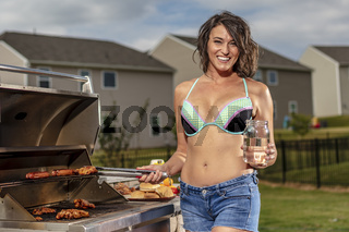 A Happy Young Wife Cooking On A Grille Before A Party