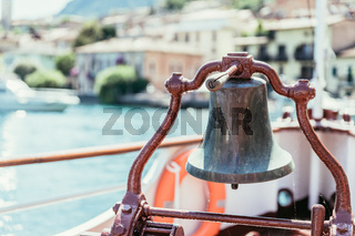 Boat tour: Boat bow with boat bell, view over azure blue water, mountain range and little village. Lago di Garda, Italy