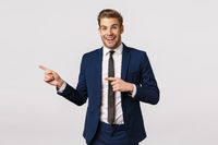 Surprised, cheerful handsome blond guy in classic suit, pointing left and smiling amused, hearing wonderful event nearby, standing white background joyful, promote product