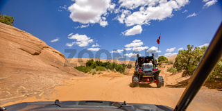 Off roading in Moab under blue sky with clouds